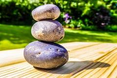 Drie opgestapelde stenen op de oppervlakte van het pijnboomhout stock foto's