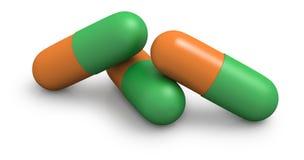 Drie oranje en groene capsules sluiten omhoog Stock Afbeeldingen