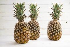 Drie organische ananasvruchten op wit geschilderd hout Stock Foto's