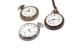 Drie oude horloges die op wit worden geïsoleerde stock foto