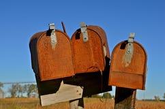 Drie oude roestige landelijke brievenbussen Stock Foto's