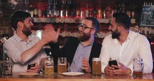 Drie oude vrienden die smartphones zitting in de bierbar gebruiken De gebaarde mens toont interessant materiaal op zijn Smartphon stock videobeelden