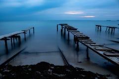 Drie oude woodern bruggen die in de open zee leiden stock foto's