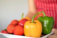 Drie paprika's op een houten achtergrond, Kokende plantaardige salade met verse paprika Royalty-vrije Stock Foto's