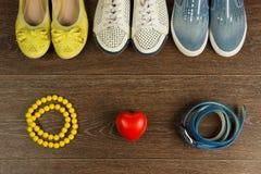 Drie paren van vrouwen` s schoenen, parels, een blauwe riem en een rood horen Stock Fotografie