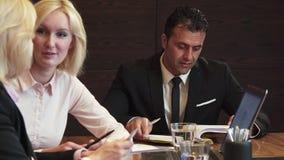 Drie partners kwamen in het bureau voor een commerciële vergadering samen stock video