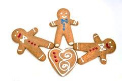 Drie peperkoekmensen met een geïsoleerd koekjeshart Stock Afbeeldingen