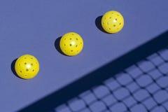 Drie Pickleballs op Hof met Netto Schaduw royalty-vrije stock fotografie