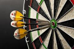 Drie pijltjes in bullseye van dartboard stock foto