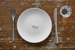 Drie pillen op plaatmes en vork royalty-vrije stock foto