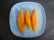 Drie plakken van meloen op een blauwe ceramische plaat Stock Afbeelding