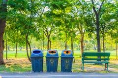 Drie plastic bakken en bank tussen haakjes in het park met aard Royalty-vrije Stock Foto