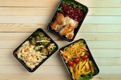 Drie plastic containers met gebraden kippenvleugels en rauwe groenten op rustieke achtergrond, kersentomaat en micro- greens stock foto's