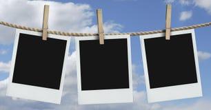 Drie polaroids die met blauwe hemel hangen Stock Fotografie