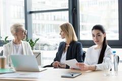drie professionele verschillende leeftijdsonderneemsters op vergadering stock foto