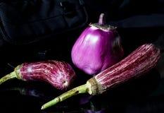 Drie purpere aubergines op zwarte achtergrond stock afbeeldingen