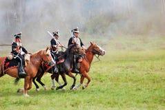 Drie reenactors kleedden zich aangezien Napoleonic oorlogsmilitairen paarden berijden Royalty-vrije Stock Afbeeldingen