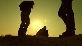 Drie reizigers dalen van een heuvel in stralen van zon nadat andere voorbij horizon gaat Groepswerk van bedrijfsmensen stock video