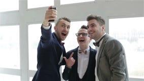 Drie representatieve aantrekkelijke knappe mensen in kostuums en vlinderdassen die selfie dichtbij het grote venster maken stock videobeelden