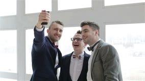 Drie representatieve mensen in kostuums en vlinderdassen die selfie dichtbij het grote venster maken stock video