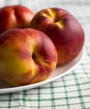 Drie rijpe nectarines op de lijst Stock Afbeeldingen