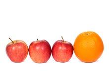 Drie rode appelen en sinaasappel Stock Foto