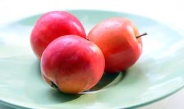 Drie rode appelen liggen op een groene plaat Stock Foto's