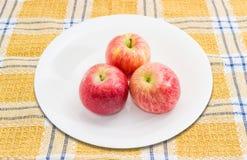 Drie rode appelen op een witte schotel Stock Foto