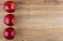 Drie rode appelen van linkerkant houten lijst Royalty-vrije Stock Afbeeldingen