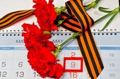 Drie rode die anjers met George lint op de kalender met 9 Mei-datum worden verpakt - Victory Day-stilleven Royalty-vrije Stock Foto