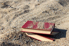 Drie rode die boeken op het zand, met zand, concept wordt behandeld transience van tijd, vertroebelden achtergrond Royalty-vrije Stock Foto's
