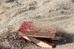 Drie rode die boeken op het zand, met zand, concept wordt behandeld transience van tijd, vertroebelden achtergrond Royalty-vrije Stock Foto