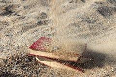 Drie rode die boeken op het zand, met zand, concept wordt behandeld transience van tijd, vertroebelden achtergrond Royalty-vrije Stock Afbeeldingen