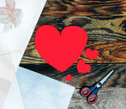 Drie rode die harten van document en schaar op de oude donkere houten grungeachtergrond worden gemaakt Royalty-vrije Stock Fotografie