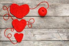 Drie rode gebreide harten op een grijze houten achtergrond, het symboliseren houden van en familie Familieverhouding, banden stock afbeeldingen