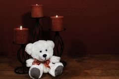 Drie rode kaarsen in metaalholoders en rood namen, één teddybeer op houten lijst toe royalty-vrije stock afbeelding