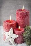 Drie rode kaarsen op grijze achtergrond, Kerstmisdecoratie Adve Royalty-vrije Stock Afbeelding