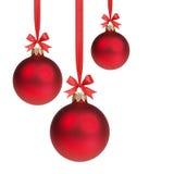 Drie rode Kerstmisballen die op lint met bogen hangen Stock Foto