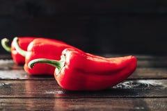 Drie rode paprika's op houten achtergrond met waterdalingen Stock Fotografie