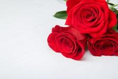 Drie rode rozen op witte houten achtergrond exemplaarruimte - Valentijnskaarten en 8 Maart-Moeder de Dagconcept van Vrouwen stock fotografie