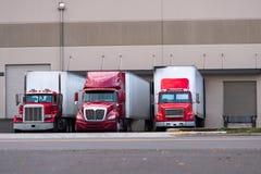 Drie rode semi vrachtwagens zijn onder het dok voor ladingsaanhangwagens stock fotografie