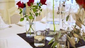 Drie rode spoelrozen in een vaas op tafel in een restaurant stock video