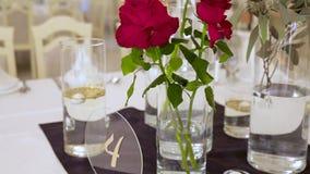 Drie rode spoelrozen in een vaas op tafel in een restaurant stock videobeelden