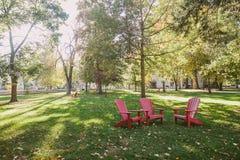 Drie rode stoelen in het park Stock Afbeelding