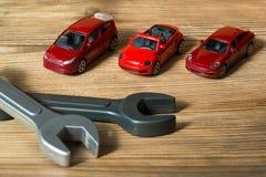 Drie rode stuk speelgoed auto's en stuk speelgoed moersleutels op een houten achtergrond stock foto's