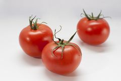 Drie rode tomaten op zwarte stock afbeelding