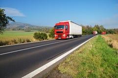 Drie rode vrachtwagens op de weg in het platteland Royalty-vrije Stock Fotografie