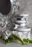 Drie ronde vakjes van de vieringsgift met zilveren lint buigt op wit lijst en boeket van orchideeën Gestapeld stelt binnen voor Stock Foto