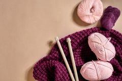 Drie roze breiend garenballen, breinaalden en en purpere gebreide plaid hoogste mening stock fotografie