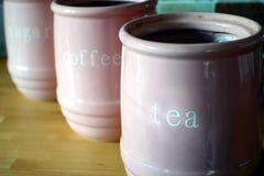 Drie roze kruiken op een houten oppervlakte van het keukenwerk, met de woorden Royalty-vrije Stock Foto's